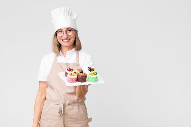 Wiek średni ładna piekarz kobieta z tortami przeciw kopii przestrzeni ścianie