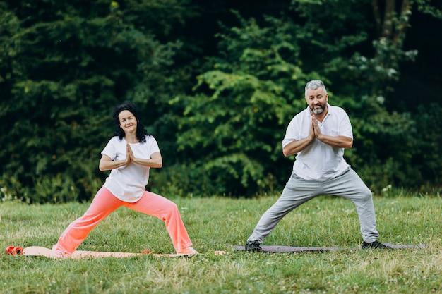Wiek średni para robi joga stoi i robi gestowi namaste joga
