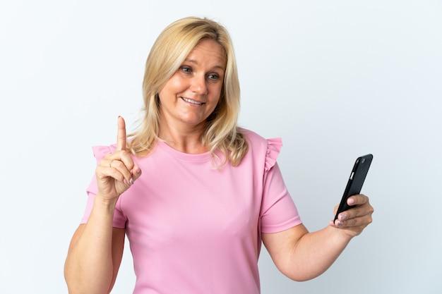 Wiek średni przy użyciu telefonu komórkowego na białym tle z zamiarem realizacji rozwiązania, podnosząc palec w górę