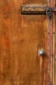 Wiekowe drewniane drzwi z zardzewiałym metalowym zamkiem