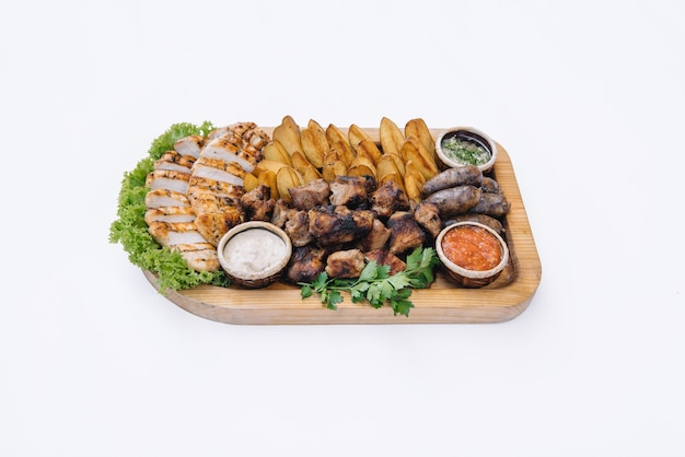 Większość dań mięsnych - szaszłyki wołowe, kiełbaski, pieczarki z grilla, ziemniaki, pomidory i sos. najlepszy wybór na piwo. zbliżenie.