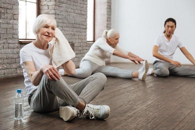 Wieku sportsmenka ubrana w odzież fitness, trzymając rękę na kolanie podczas przerwy