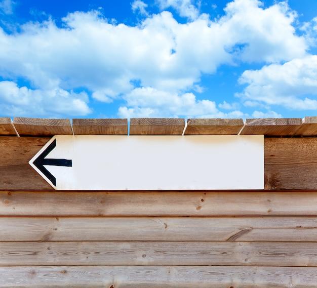 Wieku znak kierunku strzałki drewna na niebieskim niebie