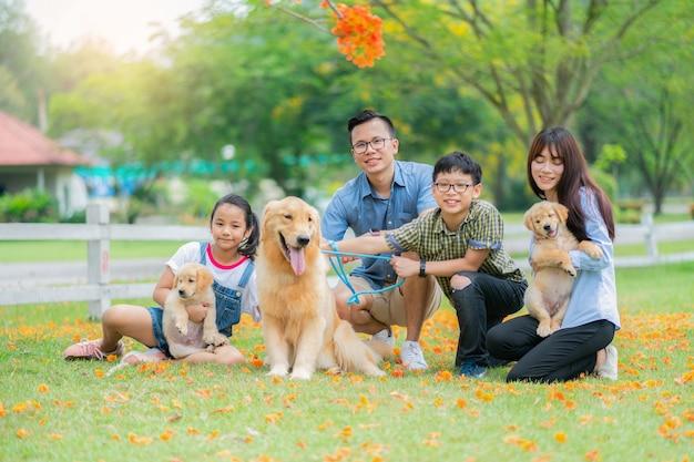 Wielbiciele rodzin i psy golden retriever odpoczywają w ogrodzie