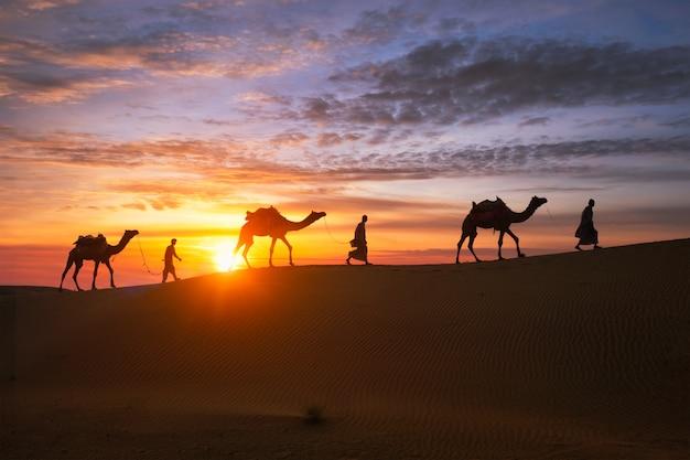 Wielbłąd indyjski cameleers kierowca z wielbłąda sylwetki w wydmy na zachód słońca. jaisalmer, radżastan, indie