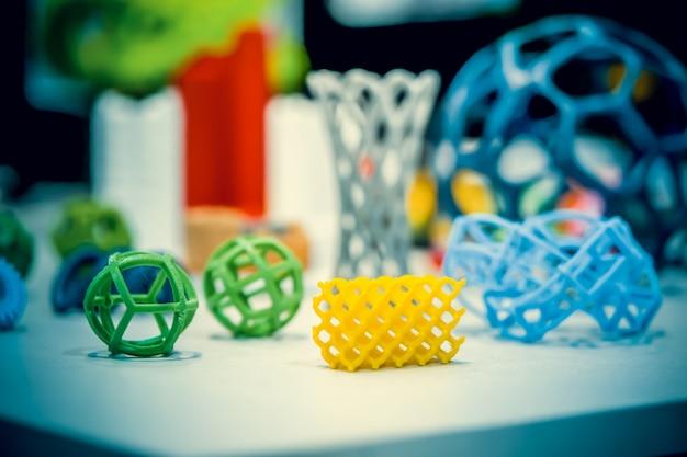 Wiele abstrakcyjnych modeli jasnych kolorowych obiektów wydrukowanych na drukarce 3d na białym stole. modelowanie osadzania topionego, fdm. progresywna nowoczesna technologia addytywna. koncepcja rewolucji przemysłowej 4.0
