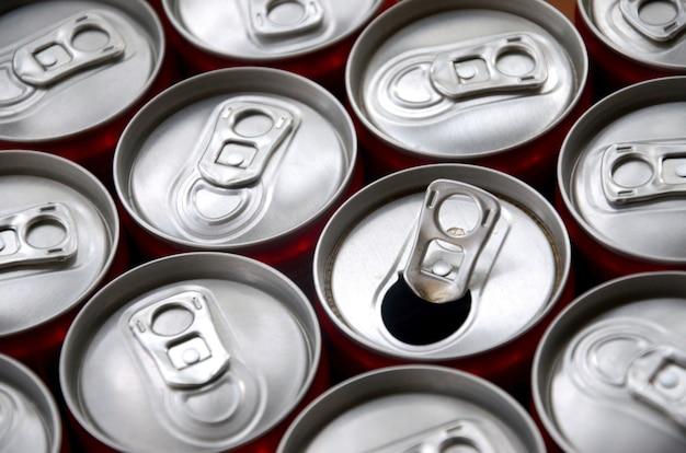 Wiele aluminiowych puszek po napojach gazowanych. reklama masowej produkcji napojów gazowanych lub puszek