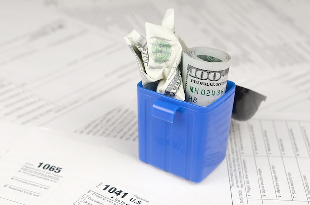 Wiele amerykańskich pustych formularzy podatkowych i zmięty banknot sto dolarów w koszu na śmieci