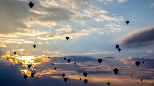Wiele balonów pasażerskich lata w chmurach na tle świtu