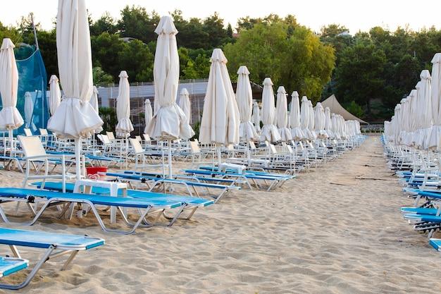 Wiele bezpłatnych leżaków wczesnym rankiem o wschodzie słońca w greckim obozie