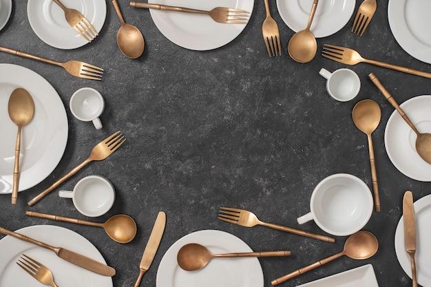 Wiele biały pusty talerz ceramiczny, kubki i mosiężne widelce, noże i łyżki na czarnym tle z miejscem na tekst.