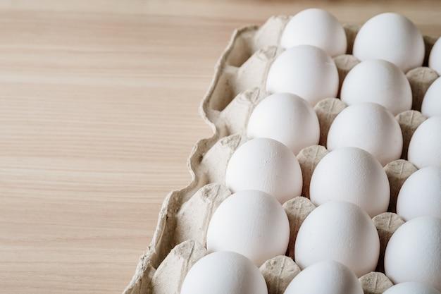 Wiele białych jaj kurzych w pudełku na tacę na drewnianym stole