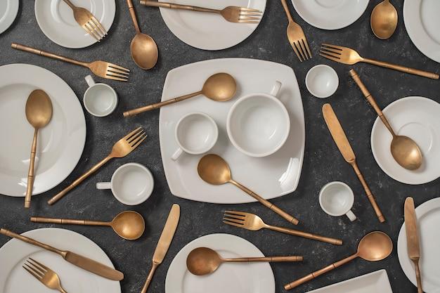 Wiele białych pustych talerzy ceramicznych, kubków i mosiężnych widelców, noży i łyżek na czarnym tle.