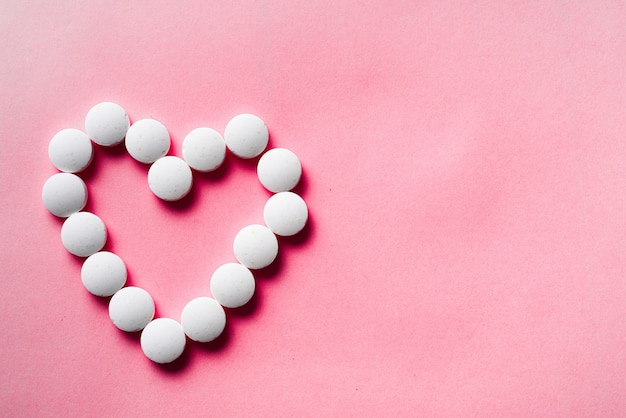 Wiele białych tabletek z serca na różowym tle. zaakceptuj koncepcję prezentów. koncepcja kardiologii lub miłości