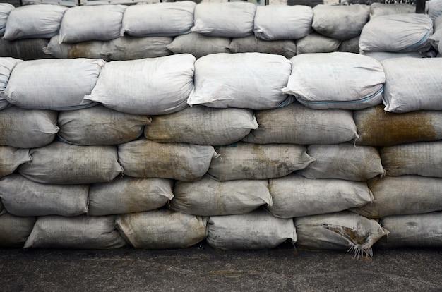 Wiele brudnych worków z piaskiem do ochrony przeciwpowodziowej. ochronna barykada z workami z piaskiem do celów wojskowych. przystojny bunkier taktyczny