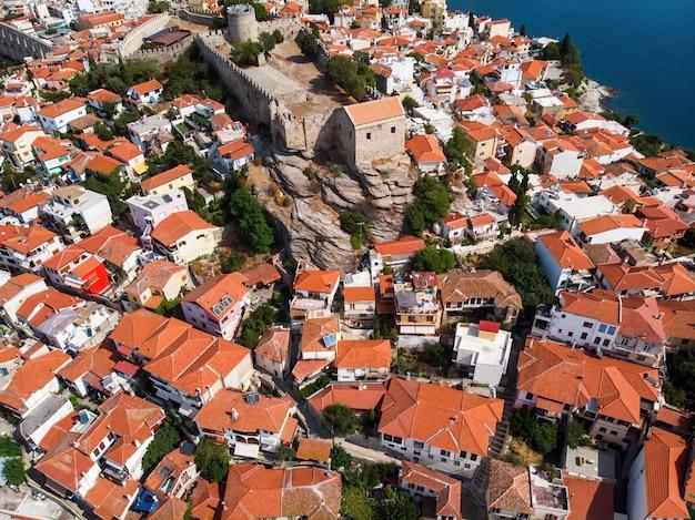 Wiele budynków z pomarańczowymi dachami i fortem, kavala, grecja