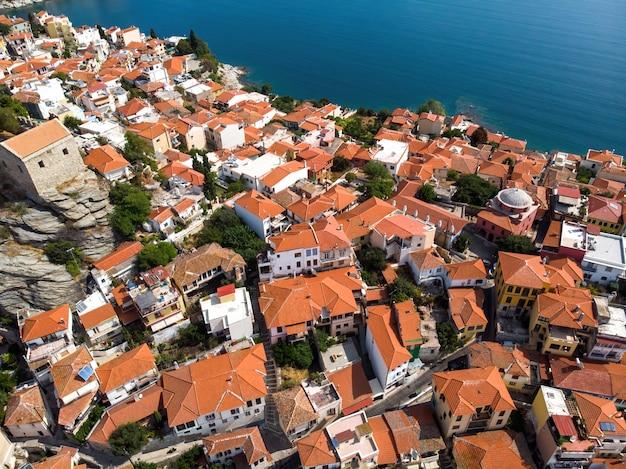 Wiele budynków z pomarańczowymi dachami, położonych na wybrzeżu morza egejskiego