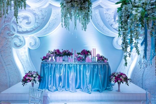 Wiele bukietów na stole w sali weselnej