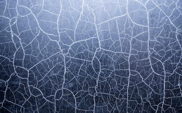 Wiele chaotycznych pęknięć na powierzchni niebieskiego materiału teksturowanego.