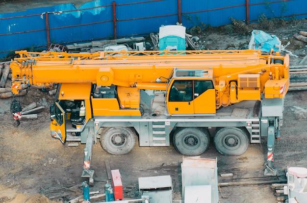 Wiele ciężarówek i dźwigów na placu składa się z podnoszenia, koła pasowego, zawiesia, żurawia gotowego do budowy.