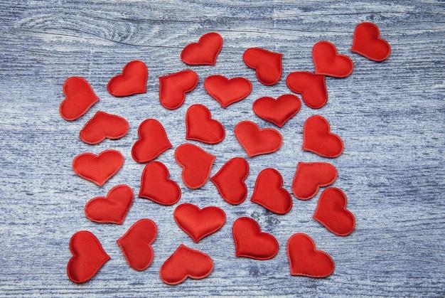 Wiele czerwoni serca na drelichowym drewnianym tle.