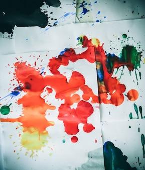 Wiele czerwonych plam na białym papierze ze smugami. streszczenie kreatywne plamy farby na białym tle. czerwone jasne kolory. poplamiony i poplamiony stół