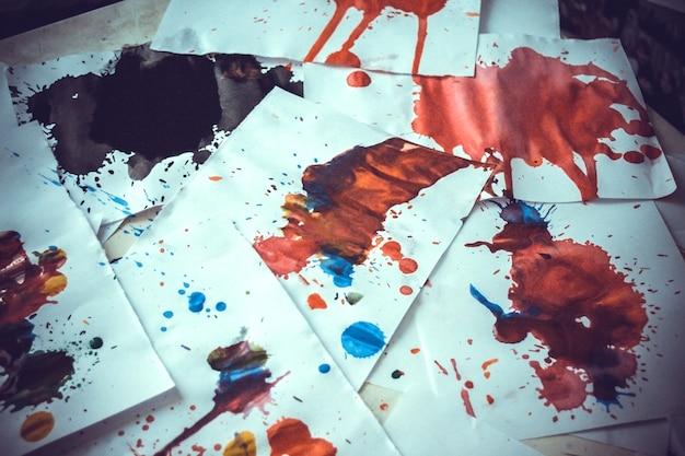 Wiele czerwonych plam na białym papierze ze smugami