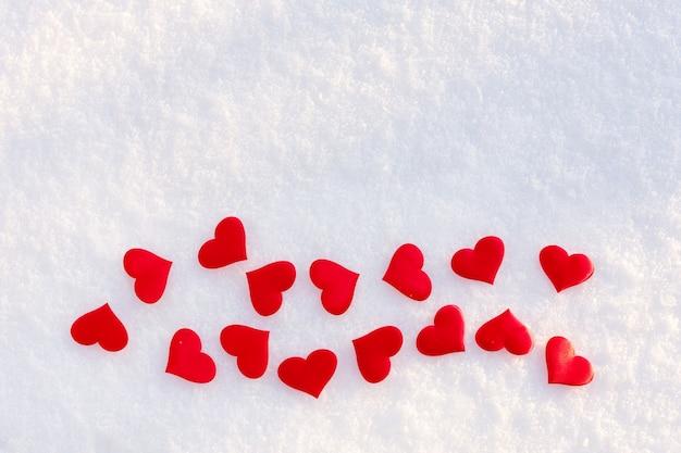 Wiele czerwonych serc leżących na białym czystym śniegu w słoneczny zimowy dzień.