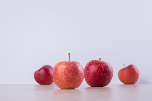Wiele czerwonych, słodkich jabłek na białym tle.