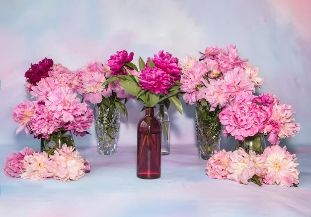 Wiele delikatnych wielobarwnych piwonii w różnych wazonach na stole miejsce na tekst