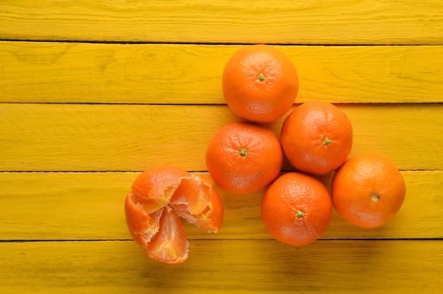 Wiele dojrzałych mandarynek na żółtym drewnianym stole. widok z góry. koncepcja owoców.