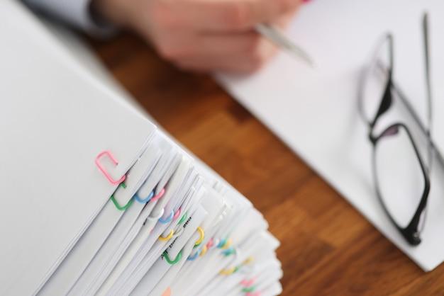 Wiele dokumentów z kolorowymi spinaczami leżącymi na zbliżeniu na pulpicie