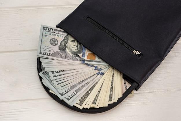 Wiele dolarów w pobliżu portfela mężczyzny, koncepcja oszczędności