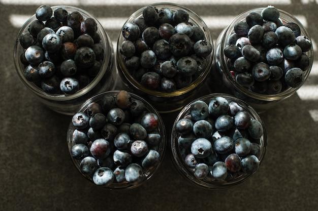 Wiele dużych, pięknych, soczystych świeżych jagód leży w szklanych słoikach