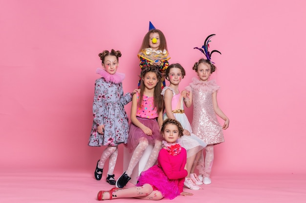 Wiele dzieci w strojach na różowym tle. wszystkiego najlepszego z okazji urodzin. świętujemy. wiele dzieci w kostiumach na halloween