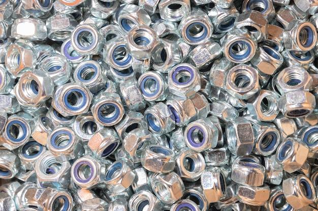 Wiele gumowanych nakrętek na tle śrub i wkrętów