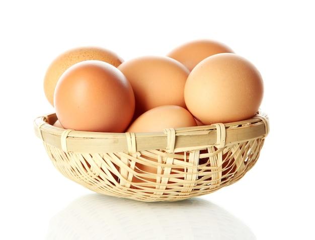 Wiele jajek w koszyku na białym tle