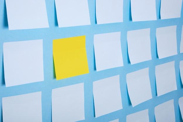 Wiele jasnoniebieskich i jedna żółta papierowa naklejka na niebieskiej powierzchni