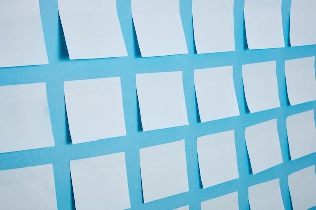 Wiele jasnoniebieskich papierowych naklejek na niebieskiej powierzchni