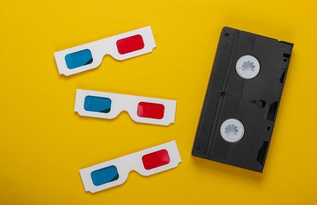 Wiele jednorazowych papierowych okularów 3d firmy anaglyph i kasety wideo na żółtej powierzchni. media retro, rozrywka lata 80-te. widok z góry
