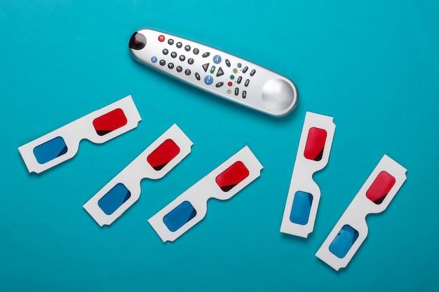 Wiele jednorazowych papierowych okularów 3d firmy anaglyph i pilota do telewizora na niebieskiej powierzchni. czas na telewizję. widok z góry