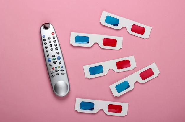 Wiele jednorazowych papierowych okularów 3d firmy anaglyph i pilota do telewizora na różowej powierzchni. czas na telewizję. widok z góry
