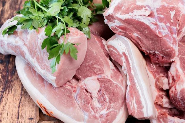 Wiele kawałków świeżego mięsa wieprzowego na drewnianej desce do krojenia