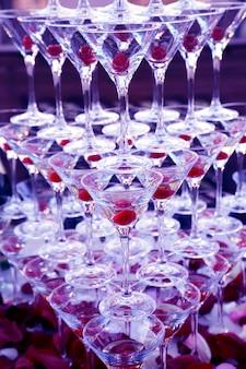 Wiele kieliszków do szampana stało jeden na drugim. zastawa stołowa na napoje