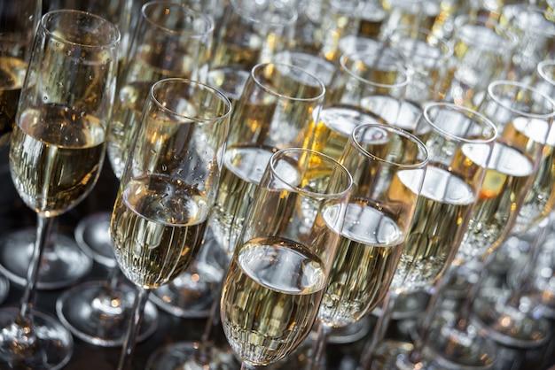 Wiele kieliszków z szampanem stoi w rzędzie. kieliszki z szampanem z bliska