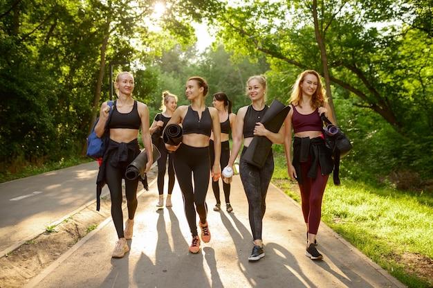 Wiele kobiet z matami, grupowe treningi jogi w letnim parku