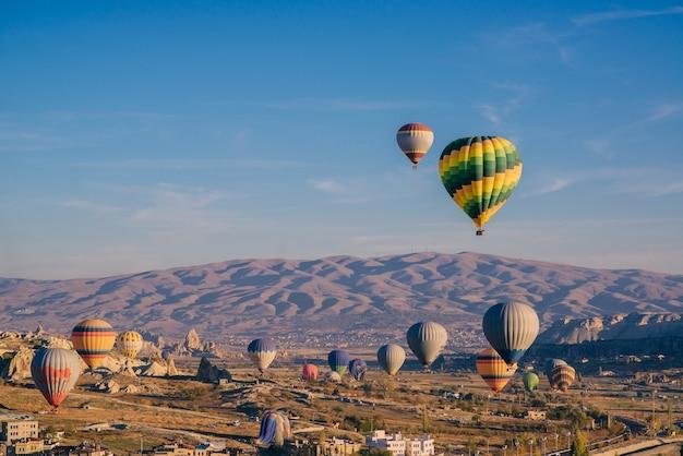 Wiele kolorowych balonów na niebie nad górami