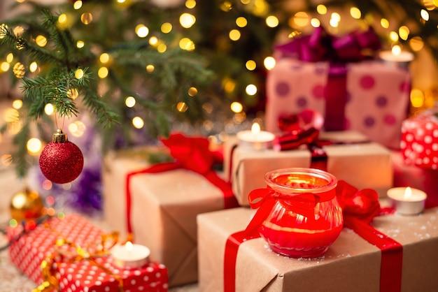 Wiele kolorowych, jasnych pudełek na prezenty pod choinką z kilkoma płonącymi świecami