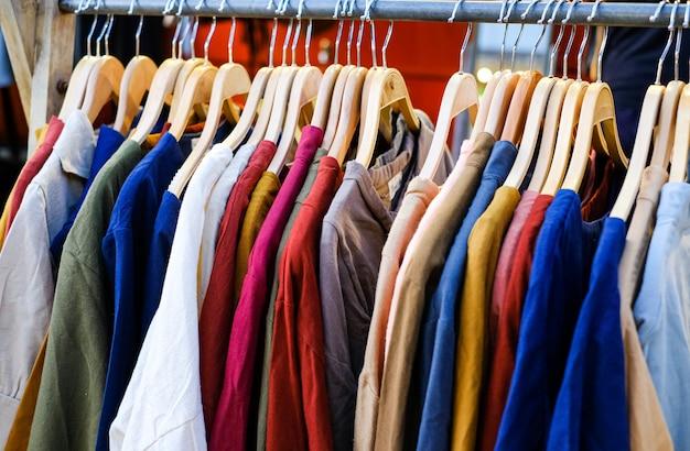 Wiele kolorowych koszulek w sklepie wisi na wieszaku