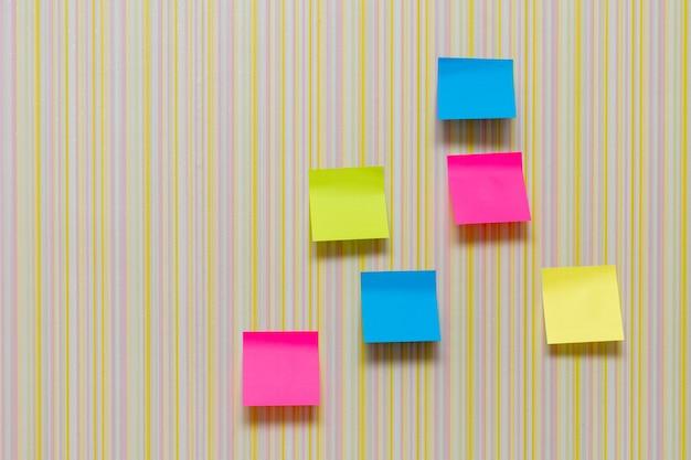 Wiele kolorowych naklejek pamięciowych na tle w paski puste miejsce na wielokolorowych naklejkach biurowych